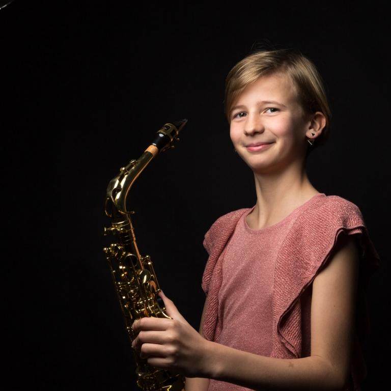 Felice speelt saxofoon tijdens haar communieshoot in de studio