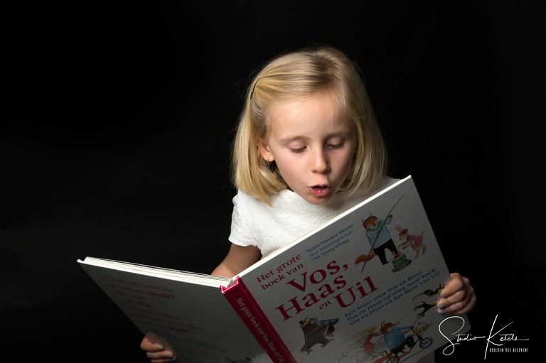 Communieportret van Augustine. Zij leest voor uit het grote boek van vos haas en uil. Intiem studioportret bij Studio Ketels
