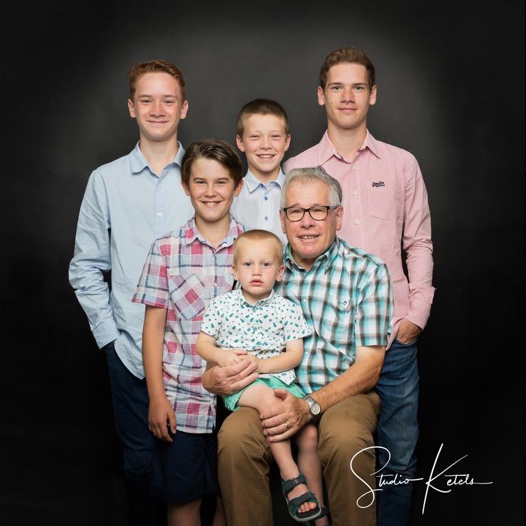 Familieportret van grootvader met 5 kleinkinderen; allen jongens. Studioportret op zwarte achtergrond bij Studio Ketels