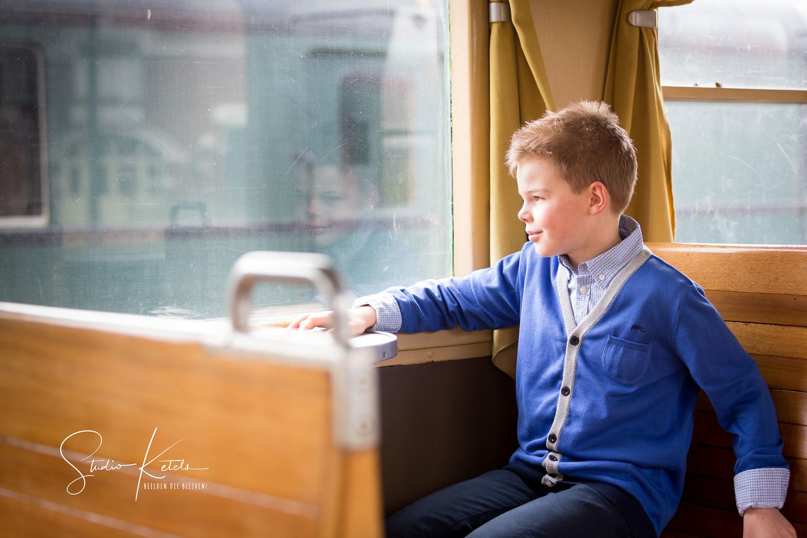 Communieportret van een jongen in de trein. Hij kijkt naar buiten, en wij zien zijn spiegelbeeld in het raam. Portret door Studio Ketels