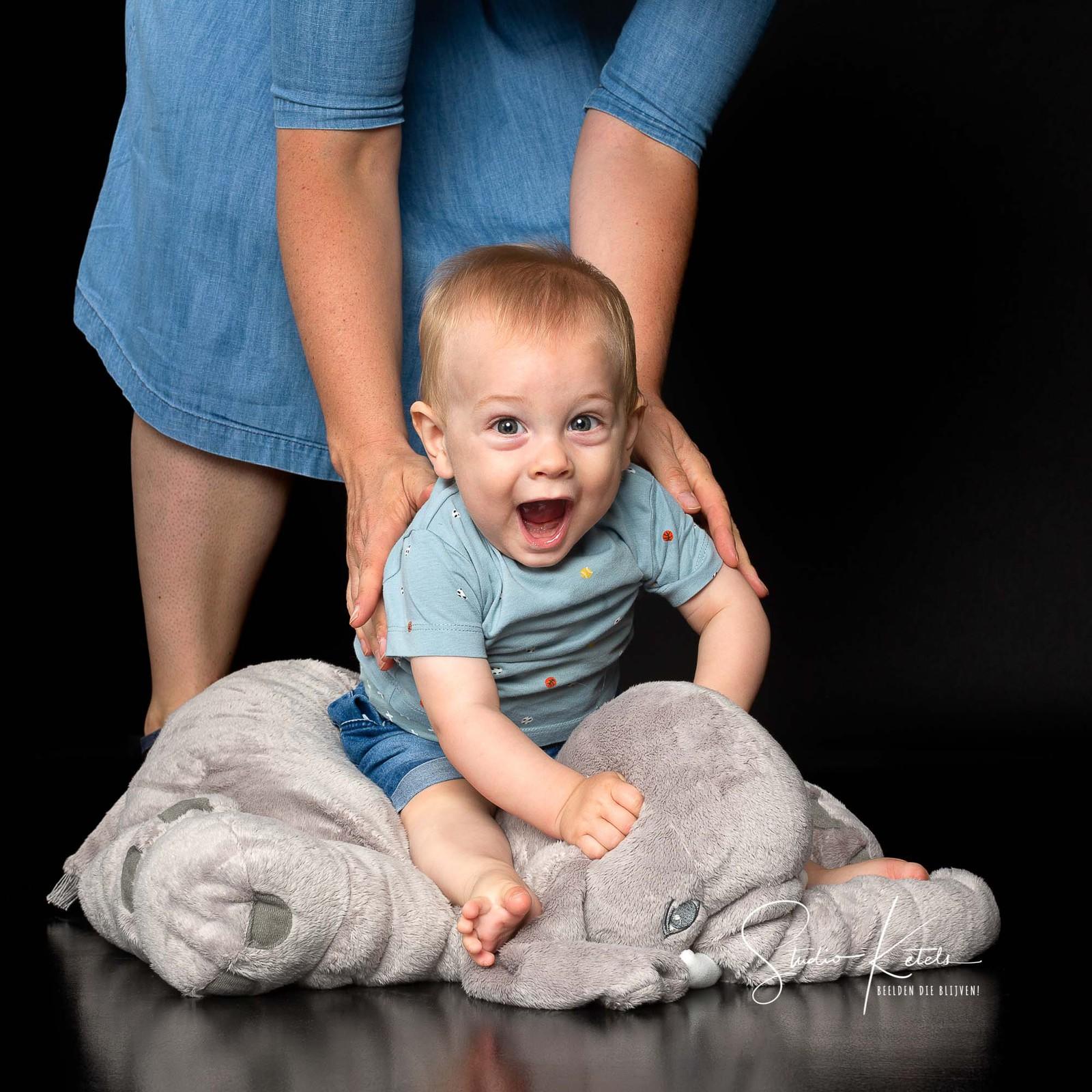 portret van een vrolijk lachende baby, die bovenop een knuffel-olifant wordt gezet. hij giert het uit en kijkt recht in de lens. portret door studio ketels