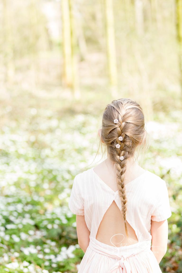 Portret van een meisje, starend in de verte, kijkend naar het bloementapijt van bosanemoontjes. Ze heeft een zacht roze jurkje aan en een heel lange vlecht met witte bloemetjes. Portret door Studio Ketels
