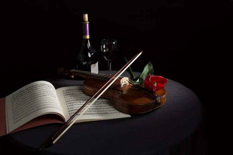 Stilleven viool met partituur en fles wijn. Fotografe Karen Ketels toont met dit beeld de stilte, van een liggende viool op een oude partituur.