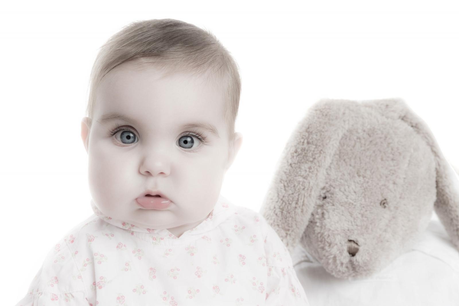 Babyportret door Studio Ketels. Baby die net kan zitten, kijkt recht in de lens. Naast haar zit een groot knuffelbeest. Beiden zijn even groot.