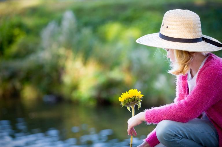 meisje met een strooien hoed, kijkt dromerig naar het water, en heeft een zonnebloem in haar hand
