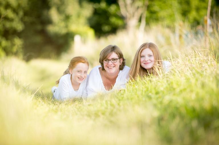 Mama met 2 tienerdochters, allen rost, in het zomergroene gras. Foto door Studio Ketels