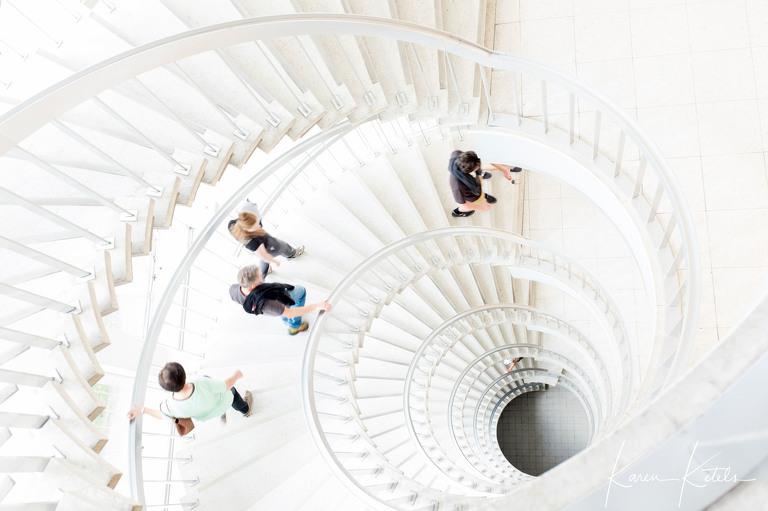 Spiraaltrap met mensen die naar beneden wandelen. Architectuurportret door Studio Ketels
